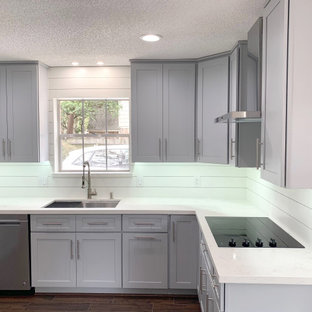 This is an example of a mid-sized transitional kitchen in Houston with a single-bowl sink, shaker cabinets, grey cabinets, quartzite benchtops, white splashback, shiplap splashback, stainless steel appliances, laminate floors, brown floor and white benchtop.