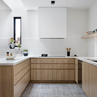 Photo of a mid-sized contemporary u-shaped kitchen in Melbourne with a double-bowl sink, quartz benchtops, white splashback, black appliances, porcelain floors, flat-panel cabinets and light wood cabinets.