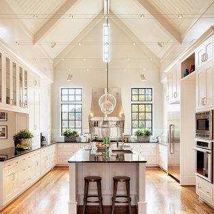 Пример оригинального дизайна: огромная п-образная кухня в классическом стиле с фасадами в стиле шейкер, белыми фасадами, техникой из нержавеющей стали, врезной раковиной, столешницей из гранита, паркетным полом среднего тона, островом и черной столешницей