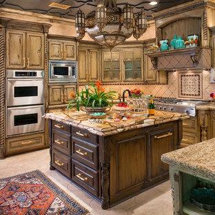 ダラスの地中海スタイルのおしゃれなキッチン (レイズドパネル扉のキャビネット、ヴィンテージ仕上げキャビネット、ベージュキッチンパネル、シルバーの調理設備の) の写真
