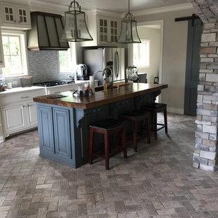 Bild på ett avskilt, mellanstort vintage vit vitt parallellkök, med en undermonterad diskho, luckor med upphöjd panel, vita skåp, träbänkskiva, grått stänkskydd, stänkskydd i stickkakel, rostfria vitvaror, tegelgolv, en köksö och grått golv