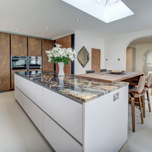 This is an example of a large contemporary eat-in kitchen in London with white cabinets, granite benchtops, metallic splashback, glass tile splashback, black appliances, with island, grey floor and orange benchtop.