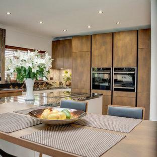 Große Moderne Wohnküche mit weißen Schränken, Granit-Arbeitsplatte, Küchenrückwand in Metallic, Rückwand aus Glasfliesen, schwarzen Elektrogeräten, Kücheninsel, grauem Boden und oranger Arbeitsplatte in London