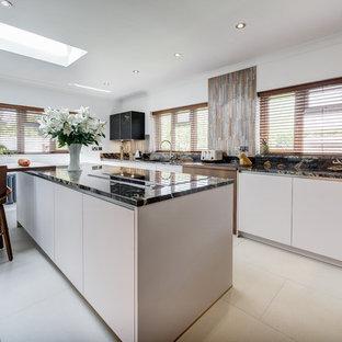 Idee per una grande cucina abitabile minimal con ante bianche, top in granito, paraspruzzi a effetto metallico, paraspruzzi con piastrelle di vetro, elettrodomestici neri, isola, pavimento grigio e top arancione