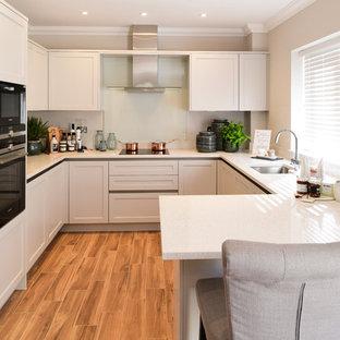 ロンドンの中サイズのトランジショナルスタイルのおしゃれなキッチン (磁器タイルの床、茶色い床、アンダーカウンターシンク、落し込みパネル扉のキャビネット、グレーのキャビネット、ガラス板のキッチンパネル、白いキッチンカウンター、ベージュキッチンパネル、パネルと同色の調理設備) の写真