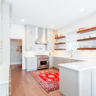 Mid-sized trendy u-shaped medium tone wood floor and brown floor kitchen photo in Austin with an undermount sink, shaker cabinets, gray cabinets, white backsplash, subway tile backsplash, stainless steel appliances, a peninsula, white countertops and quartz countertops