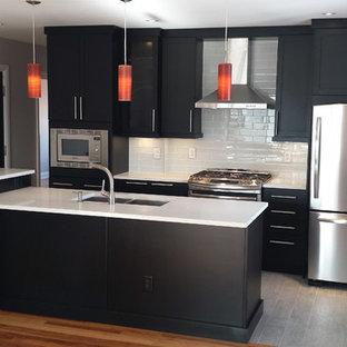 トロントの小さいモダンスタイルのおしゃれなキッチン (アンダーカウンターシンク、シェーカースタイル扉のキャビネット、黒いキャビネット、クオーツストーンカウンター、白いキッチンパネル、サブウェイタイルのキッチンパネル、シルバーの調理設備の、セラミックタイルの床) の写真