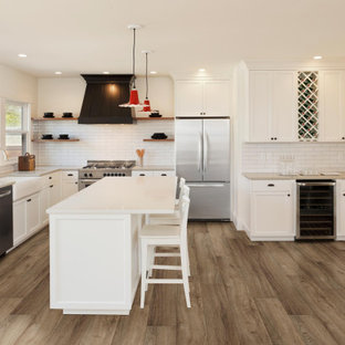 Photo of an expansive kitchen in Other with recessed-panel cabinets, white cabinets, white splashback, subway tile splashback, stainless steel appliances, vinyl floors, with island, brown floor and white benchtop.