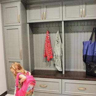 他の地域の広いおしゃれなキッチン (アンダーカウンターシンク、フラットパネル扉のキャビネット、グレーのキャビネット、クオーツストーンカウンター、グレーのキッチンパネル、ガラスタイルのキッチンパネル、シルバーの調理設備、セラミックタイルの床、グレーの床、白いキッチンカウンター) の写真