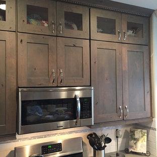 デンバーの広いラスティックスタイルのおしゃれなキッチン (アンダーカウンターシンク、シェーカースタイル扉のキャビネット、中間色木目調キャビネット、珪岩カウンター、白いキッチンパネル、セラミックタイルのキッチンパネル、シルバーの調理設備、リノリウムの床) の写真