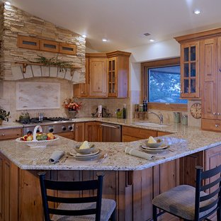 Inspiration for a mid-sized rustic u-shaped ceramic floor eat-in kitchen remodel in Denver with a double-bowl sink, raised-panel cabinets, distressed cabinets, granite countertops, beige backsplash, ceramic backsplash, stainless steel appliances and a peninsula