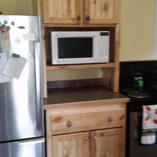 ボイシのカントリー風おしゃれなキッチン (シェーカースタイル扉のキャビネット、ヴィンテージ仕上げキャビネット、ベージュキッチンパネル、石タイルのキッチンパネル、パネルと同色の調理設備) の写真