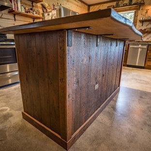 Esempio di una piccola cucina rustica con lavello stile country, ante in stile shaker, ante con finitura invecchiata, top in cemento, paraspruzzi marrone, paraspruzzi in legno, elettrodomestici in acciaio inossidabile, pavimento in cemento, isola e pavimento grigio