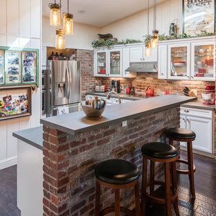Idee per una cucina stile rurale di medie dimensioni con ante di vetro, ante bianche, top in cemento, paraspruzzi marrone, paraspruzzi in mattoni, elettrodomestici in acciaio inossidabile, parquet scuro, isola, pavimento marrone e top grigio