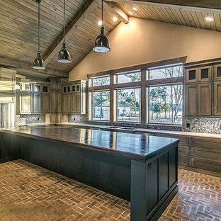 Bild på ett stort, avskilt rustikt u-kök, med rostfria vitvaror, tegelgolv, en köksö, en dubbel diskho, skåp i shakerstil, skåp i mellenmörkt trä, träbänkskiva, flerfärgad stänkskydd och stänkskydd i stenkakel