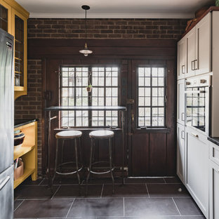 Design ideas for a small country l-shaped separate kitchen in Philadelphia with a double-bowl sink, shaker cabinets, grey cabinets, soapstone benchtops, white splashback, terra-cotta splashback, stainless steel appliances, slate floors, no island, purple floor and black benchtop.