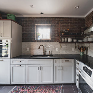 This is an example of a small country l-shaped separate kitchen in Philadelphia with a double-bowl sink, shaker cabinets, grey cabinets, soapstone benchtops, white splashback, terra-cotta splashback, stainless steel appliances, slate floors, no island, purple floor and black benchtop.
