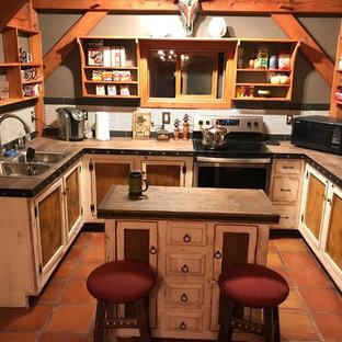 Foto på ett litet rustikt brun kök, med en nedsänkt diskho, vita skåp, kaklad bänkskiva, vitt stänkskydd, stänkskydd i mosaik, rostfria vitvaror, klinkergolv i terrakotta, en köksö och orange golv
