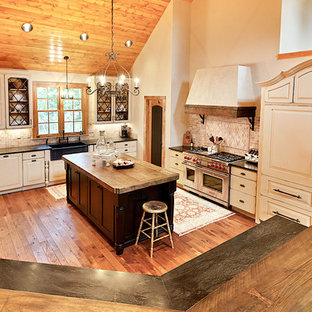 Large farmhouse enclosed kitchen ideas - Inspiration for a large country u-shaped dark wood floor enclosed kitchen remodel in Other with a farmhouse sink, raised-panel cabinets, white cabinets, wood countertops, red backsplash, paneled appliances, an island and travertine backsplash
