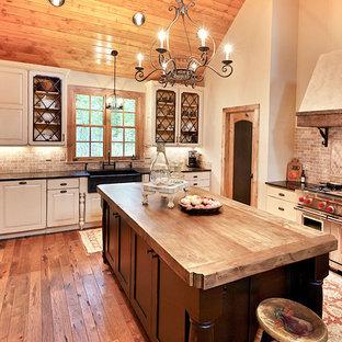 他の地域の大きいカントリー風おしゃれなキッチン (レイズドパネル扉のキャビネット、白いキャビネット、木材カウンター、赤いキッチンパネル、エプロンフロントシンク、パネルと同色の調理設備、濃色無垢フローリング、トラバーチンの床) の写真