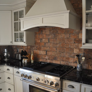 Mid-sized rustic eat-in kitchen inspiration - Example of a mid-sized mountain style u-shaped medium tone wood floor eat-in kitchen design in Baltimore with a farmhouse sink, recessed-panel cabinets, white cabinets, granite countertops, red backsplash, stone tile backsplash, stainless steel appliances and an island