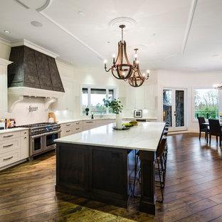 バンクーバーの巨大なラスティックスタイルのおしゃれなキッチン (アンダーカウンターシンク、シェーカースタイル扉のキャビネット、白いキャビネット、人工大理石カウンター、白いキッチンパネル、石スラブのキッチンパネル、シルバーの調理設備の、無垢フローリング、茶色い床、白いキッチンカウンター) の写真