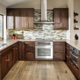 Inredning av ett modernt stort kök, med skåp i shakerstil, skåp i mörkt trä, flerfärgad stänkskydd, stänkskydd i stickkakel, rostfria vitvaror, ljust trägolv, en halv köksö, en undermonterad diskho och bänkskiva i kvarts