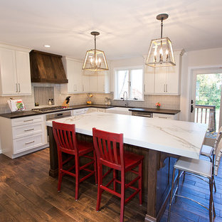 Eat-in kitchen - large transitional u-shaped dark wood floor eat-in kitchen idea in DC Metro with a farmhouse sink, shaker cabinets, white cabinets, quartz countertops, gray backsplash, subway tile backsplash, stainless steel appliances and an island