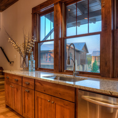 Inspiration for a large rustic l-shaped light wood floor eat-in kitchen remodel in Austin with an undermount sink, shaker cabinets, medium tone wood cabinets, granite countertops, stainless steel appliances and an island
