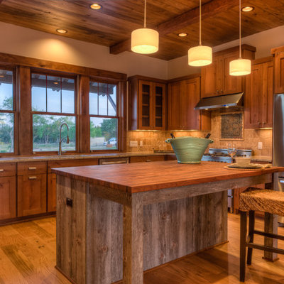 Eat-in kitchen - large rustic l-shaped light wood floor eat-in kitchen idea in Austin with shaker cabinets, stainless steel appliances, wood countertops, an undermount sink, medium tone wood cabinets, beige backsplash and an island