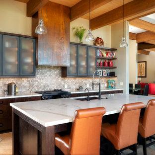 Inredning av ett amerikanskt vit vitt kök med öppen planlösning, med en undermonterad diskho, luckor med glaspanel, svarta skåp, flerfärgad stänkskydd, en köksö och orange golv