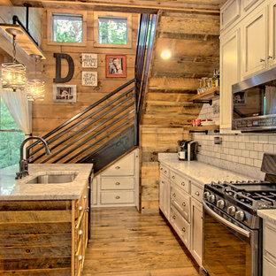 Diseño de cocina rural, pequeña, abierta, con fregadero encastrado, armarios con paneles empotrados, puertas de armario con efecto envejecido, encimera de granito, salpicadero blanco, salpicadero de azulejos de piedra, electrodomésticos de acero inoxidable, suelo de madera pintada, una isla y suelo marrón