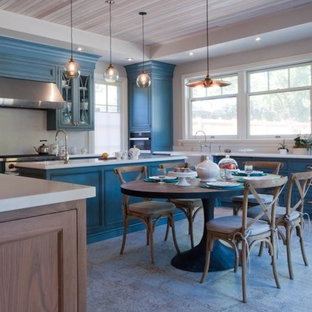 Inspiration for a large country u-shaped eat-in kitchen in Toronto with beaded inset cabinets, blue cabinets, quartzite benchtops, with island, a farmhouse sink, white splashback, stone slab splashback, stainless steel appliances and ceramic floors.