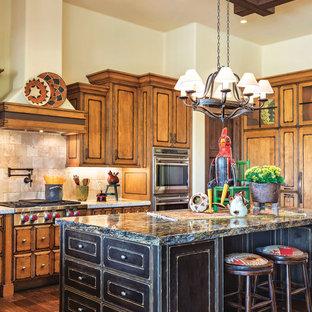 フェニックスのサンタフェスタイルのおしゃれなアイランドキッチン (中間色木目調キャビネット、ベージュキッチンパネル、シルバーの調理設備の、濃色無垢フローリング、ベージュのキッチンカウンター) の写真