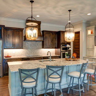 Photo of a mid-sized transitional l-shaped kitchen in Indianapolis with a drop-in sink, shaker cabinets, brown cabinets, granite benchtops, grey splashback, cement tile splashback, stainless steel appliances, vinyl floors, with island, brown floor and grey benchtop.