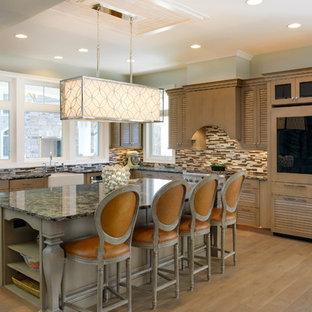 他の地域の大きいラスティックスタイルのおしゃれなキッチン (エプロンフロントシンク、ルーバー扉のキャビネット、中間色木目調キャビネット、クオーツストーンカウンター、マルチカラーのキッチンパネル、ガラスタイルのキッチンパネル、パネルと同色の調理設備、無垢フローリング) の写真