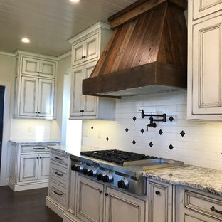 Large rural u-shaped kitchen pantry in Other with a belfast sink, beaded cabinets, distressed cabinets, granite worktops, white splashback, porcelain splashback, stainless steel appliances, dark hardwood flooring, an island and brown floors.