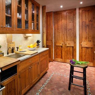 Inspiration för ett mellanstort, avskilt lantligt parallellkök, med skåp i shakerstil, skåp i mellenmörkt trä, bänkskiva i kalksten, beige stänkskydd, stänkskydd i sten, en undermonterad diskho, rostfria vitvaror, tegelgolv och rött golv