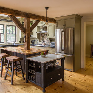 Design ideas for a large country l-shaped kitchen in Boston with a farmhouse sink, shaker cabinets, green cabinets, multi-coloured splashback, stainless steel appliances, medium hardwood floors, with island, soapstone benchtops and ceramic splashback.