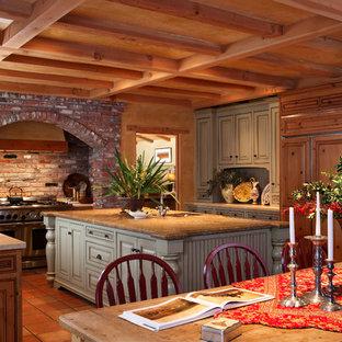 Geräumige Mediterrane Wohnküche mit Kassettenfronten, hellbraunen Holzschränken, Granit-Arbeitsplatte, bunter Rückwand, Elektrogeräten mit Frontblende, Terrakottaboden und Kücheninsel in San Francisco