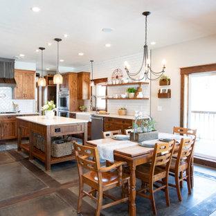 ポートランドの大きいラスティックスタイルのおしゃれなキッチン (エプロンフロントシンク、シェーカースタイル扉のキャビネット、中間色木目調キャビネット、クオーツストーンカウンター、白いキッチンパネル、サブウェイタイルのキッチンパネル、シルバーの調理設備の、コンクリートの床、グレーの床、白いキッチンカウンター) の写真