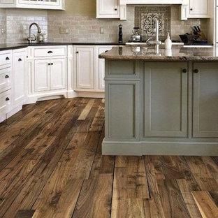 シカゴの広いラスティックスタイルのおしゃれなキッチン (白いキャビネット、御影石カウンター、マルチカラーのキッチンパネル、レンガのキッチンパネル、シルバーの調理設備、無垢フローリング、アンダーカウンターシンク、シェーカースタイル扉のキャビネット、茶色い床) の写真