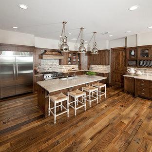 オースティンの巨大なラスティックスタイルのおしゃれなキッチン (エプロンフロントシンク、シェーカースタイル扉のキャビネット、濃色木目調キャビネット、御影石カウンター、ベージュキッチンパネル、石タイルのキッチンパネル、シルバーの調理設備の、濃色無垢フローリング、茶色い床、ベージュのキッチンカウンター) の写真