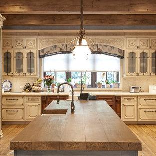 Bild på ett mycket stort rustikt brun brunt kök, med luckor med upphöjd panel, vita skåp, en köksö, en rustik diskho, träbänkskiva, beige stänkskydd, stänkskydd i mosaik, rostfria vitvaror, målat trägolv och gult golv