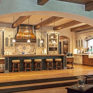 Esempio di una grande cucina chic con ante con bugna sagomata, isola, lavello stile country, ante beige, paraspruzzi beige, elettrodomestici da incasso, pavimento in legno massello medio, pavimento marrone e top beige