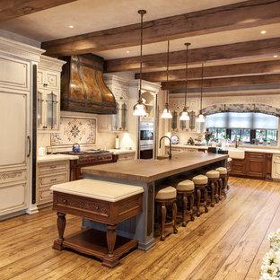 Offene, Geräumige Urige Küche in L-Form mit profilierten Schrankfronten, weißen Schränken, Kücheninsel, Küchenrückwand in Beige, Rückwand aus Mosaikfliesen, Landhausspüle, Arbeitsplatte aus Holz, Küchengeräten aus Edelstahl, gebeiztem Holzboden, gelbem Boden und brauner Arbeitsplatte in New York