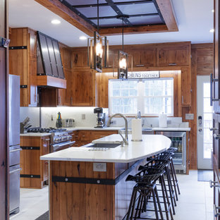 Photo of an expansive arts and crafts u-shaped open plan kitchen in Atlanta with a farmhouse sink, flat-panel cabinets, light wood cabinets, quartz benchtops, white splashback, stone slab splashback, stainless steel appliances, marble floors, with island, white floor and white benchtop.