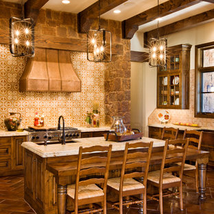 This is an example of a large country u-shaped eat-in kitchen in Austin with a farmhouse sink, raised-panel cabinets, dark wood cabinets, granite benchtops, beige splashback, ceramic splashback, stainless steel appliances, ceramic floors, with island, red floor and beige benchtop.