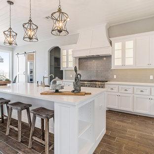 Idéer för ett lantligt kök, med bänkskiva i kvartsit, beige stänkskydd, stänkskydd i glaskakel, rostfria vitvaror, målat trägolv, en köksö och brunt golv