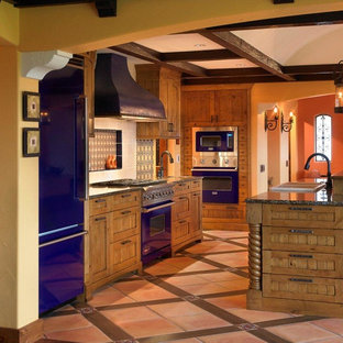 Inspiration for a mid-sized country galley eat-in kitchen in Phoenix with a drop-in sink, recessed-panel cabinets, medium wood cabinets, coloured appliances, multi-coloured floor, terra-cotta floors and granite benchtops.